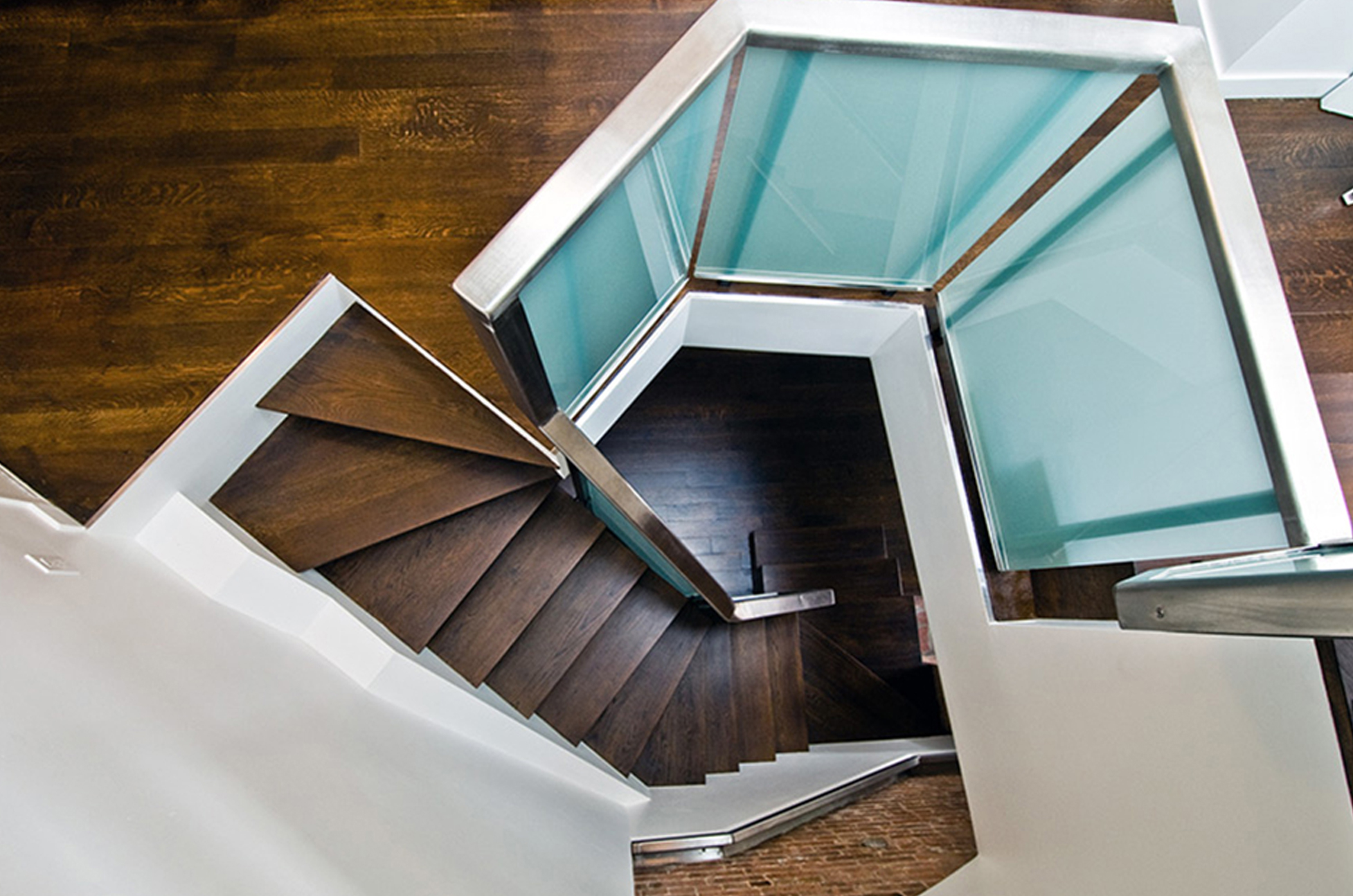 Fabricated custom steel staircase in a duplex NYC apartment. Here a NYC contractor used steel, stainless steel, stained wood and safety glass cantilever from brick wall. A nyc structurall engineer services were engaged Jane St - West Village NYC new york city
